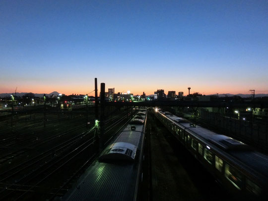 3月2日(2018) 中央線の夕暮れ:太宰陸橋とも呼ばれる三鷹電車庫跨線橋の上から立川方向を見たもの。遠くに丹沢などの山並みと富士山が望めます。昭和4年に建造された陸橋は、太宰治も好んだ場所で、鉄骨むき出し構造がとてもレトロです。