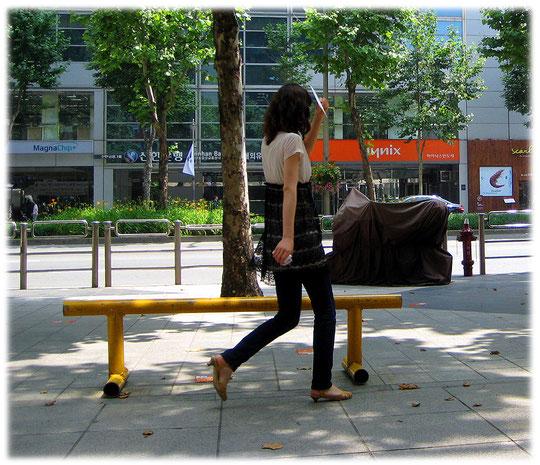 Pictures of a young Korean woman hiding her face behind some paper to avoid getting tanned. Bilder von jungen Frauen die nicht ihr Gesicht in die Sonne stecken möchten