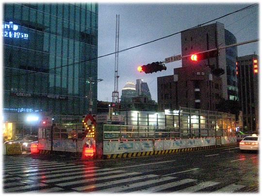 This photo is about a street construction site in a street in Seoul at Gangnam area. Bild einer Baustelle mitten auf einer Straße, mit einem rot leuchtenden Fass um die Autofahrer zu warnen.