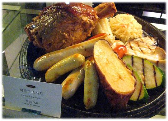This photo shows German bratwurst, haxen, sauerkraut, and meat. Restaurant at Coex, Gangnam. Foto von Haxen mit Sauerkraut und Bratuwrst und deutschem Bier im Coex Zentrum in Gangnam