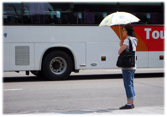 This image shows a young woman standing at a bus station and protecting her body with a sunshade. She doesn't wants to get tanned! Fotos von koreanischen Frauen die in unter einem Sonnenschirm steht