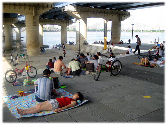 This picture shows people relaxing in the shadow beneath a bridge at a Han River park. Life at it's best! City life of Seoul in Korea. Bild von alten Koreanern im Schatten unter der Brücke