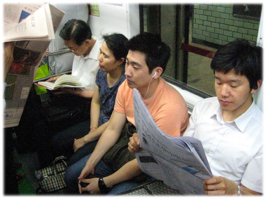 On this photo we can see Korean people sitting inside a train and reading newspaper in a crowded subway train. Foto mit Koreanern in einer U-Bahn.
