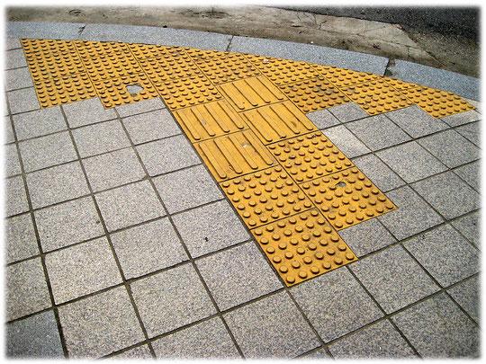 This photo shows yellow markings on the pavement for blind people on a street close to Gangnam station. Bilder von gelben Markierungen auf dem Gehsteig für Blinde und Behinderte Koreaner in Seoul