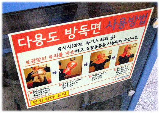 This photo gives an image of how to use the gas masks at the Seoul station. Bild von Gasmasken in einer U-Bahn-Station.