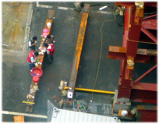 Lovely and interesting picture of workers at a construction site having lunch. Foto von Arbeitern auf einer Baustelle, die gerade ihr Mittagessen gemeinsam essen.