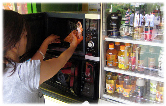 This photo shows a microwave oven at a convenience store. You use it to heat up Korean imbiss dishes and meals. Fotos von einerm Mikrowellengerät in einem koreanischen Kiosk in Seoul. Typisches Essen.