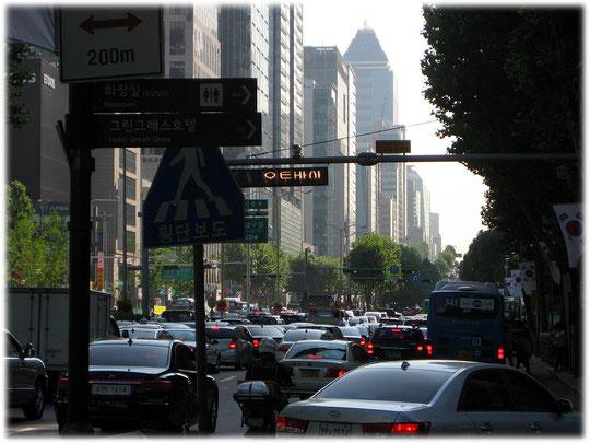 On this photo you see the busy Teheranro street full of cars and with skyscrapers in the background. Bild von der belebten Straße Teherano und den Hochhäusern im Hintergrund