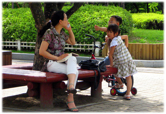 This photo shows a mother using her telephone and her two children play aside. They love Seoul like me! Bilder von spielenden Kindern und ihrer Mutter die gerade telefoniert.