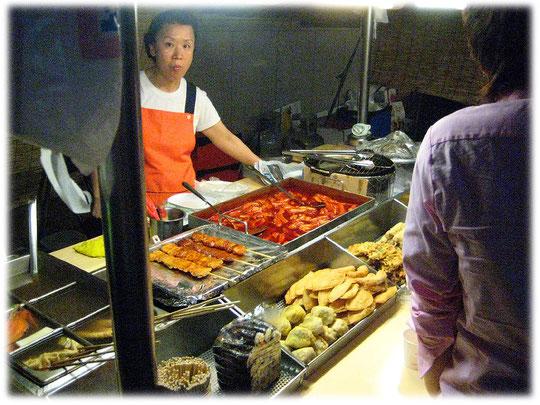 This photo shows a typical korean street food snack. Picture of a Korean cooking woman. Bilder von einer koreanischen Frau die einen Straßenimbiss betreibt und gerade kocht.