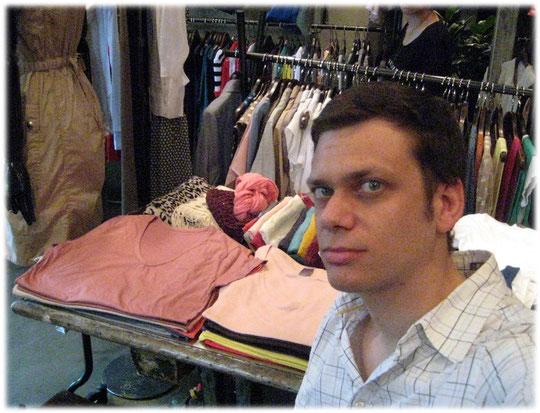 Photo of a young German man waiting for the Korean woman to finish her shopping tour. Bild eines Mannes der in einem Second Hand Laden in Seoul, Südkorea, sitzt.