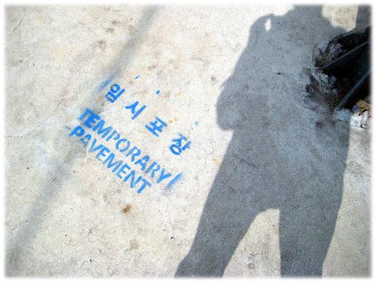 """On this photo you can see the writing """"temporary pavement"""" at a pavement construction site. Fotos von einer blauen Beschriftung auf dem Gehweg und der Straße für die Warnung der koreanischen Fußgänger"""