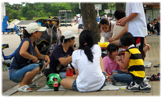Photos of a family with many children having a picnic at Han River park (Yeouido park). Bild von einer Familie mit Kindern die in einem Park spielen und Picknick machen.