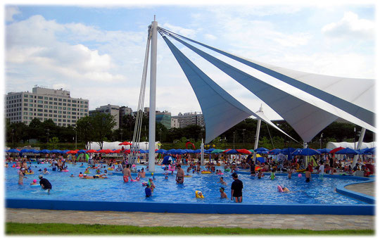 On this photo you see an open air public swimming pool full of city life. Foto von einem öffentlichen Schwimmbad und Freibad. Die koreanischen Kinder spielen und schwimmen wild umher.