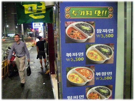 This picture shows an advertisment for Korean restaurant food with two dishes on the same table. Das Bild zeigt die Werbung eines koreanischen Pubs mit zwei Speisen pro Teller