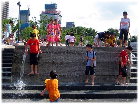 Picture of children playing with water at Han River park in the city of South Korea. Koreanische Kinder spielen mit Wasser auf einem Spielplatz in Seoul