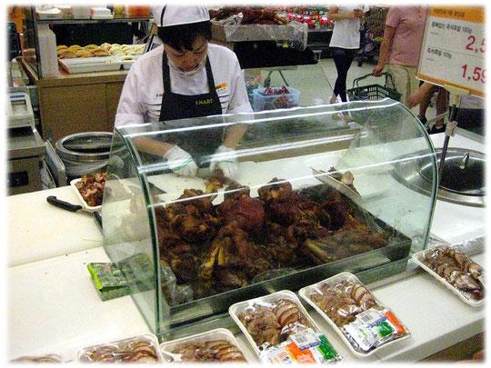 Fresh food are prepared by Korean women so that the customers can buy fresh dishes and meals. Frische asiatische Gerichte werden für die Kunden im Markt zubereitet. Der Markt liegt in Südkorea.