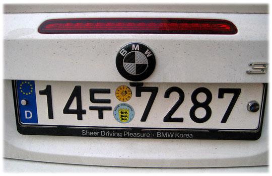 This photo shows a Korean car sign with German blue national sign at the side. Bild von einem deutschen BMW Auto PKW in den Straßen von Seoul in Südkorea.