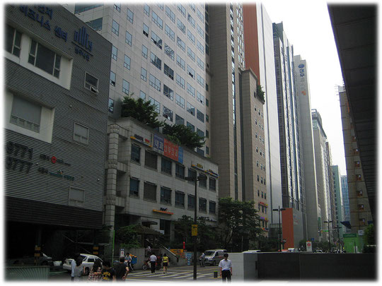 This image is about a narrow street in Seoul, on the left and on the right are really high buildings which cause shadow for the street. Bilder von Hochhäusern die eine Straße mit Schatten bewerfen