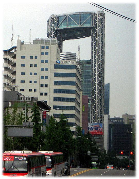 On this photo you see the Jongno tower which is a big high building full of offices. Bilder von einem großen Haus mit einer Lücke. In dem Haus sitzt das Finanzamt von Seoul.