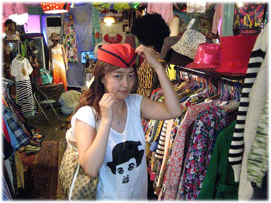 Photo of a beautiful young Korean woman who is wearing a hat inside a second hand shop in Seoul. Eine Koreanerin probiert einen Hut in einem Second Hand Laden.