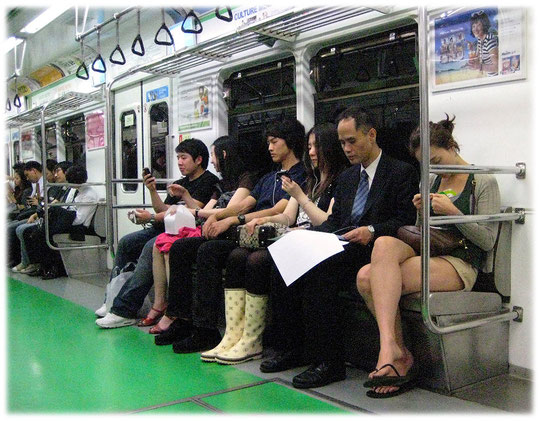 This image shows people sitting in the subway. A young woman is wearing rain boots. This is very stylish in Seoul nowadays! Bild von einer Frau mit Regenstiefeln in der U-Bahn