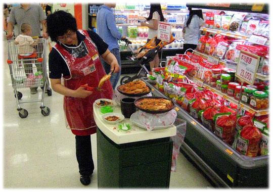 A Korean woman prepares fresh free trials of Korean food dishes inside the shop. The customers can try all meals. Koreanisches asiatisches Essen in einem asiatischen Markt in Südkorea. American food.