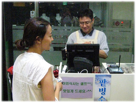 This picture shows a woman who pays the bill at the restaurant check out cash desk. Das Bild zeigt eine junge Koreanerin die das Essen im Gasthaus bezahlt