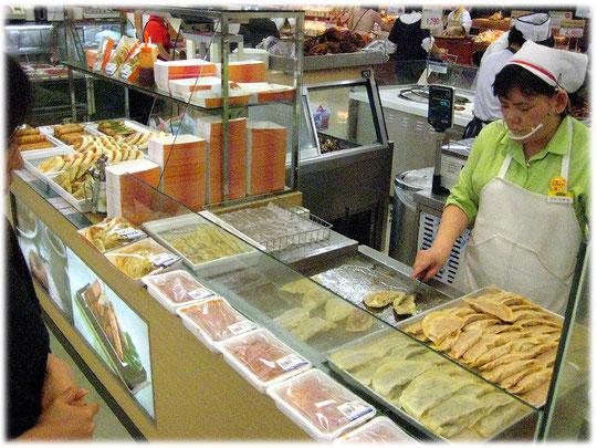 Picture of a Korean woman making some food for the shoppers and customers of the South Korean food market. Bild einer Frau die asiatisch koreanisches Essen und Gerichte vorbereitet.