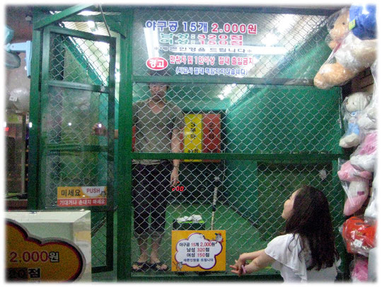 Pictures about a young man who is playing indoor baseball at a amusement shop at Gangnam area, Seoul. A young woman is watching him. Fotos von einem Koreaner in Südkorea