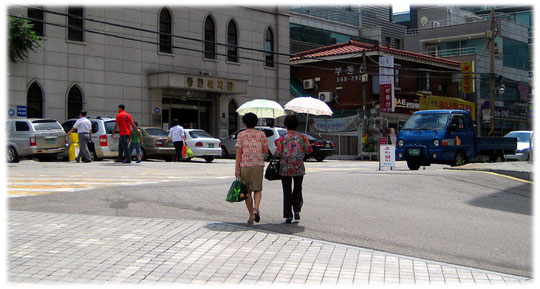 Pictures of two Korean women walking in the sunshine. But they protect their white skin with lovely sunshades in South Korea. Ein Foto von Frauen die in Südkorea Sonnenschirme tragen.