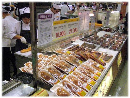 Photo of supermarket stuff preparing the fres Korean food for the shoppers and customers. Seoul, South Korea. Angestellte in einem koreanischen Geschäft bereiten das Essen für die Käufer vor.