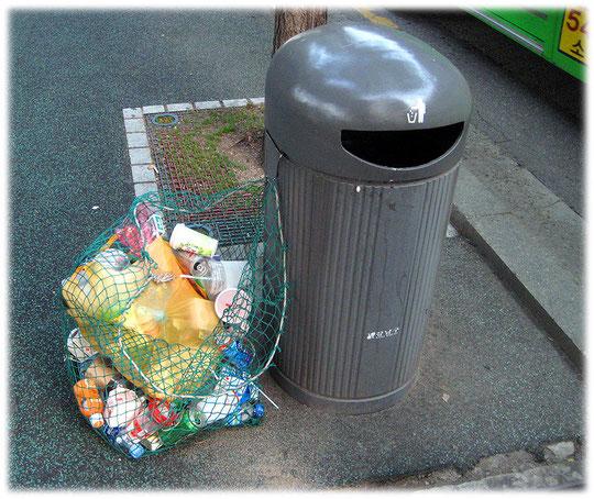 On this photo you see a street trashcan with a special net for recyclable trash. Foto von einem Abfalleimer und Mülleimer auf der Straße oder dem Gehweg in Seoul