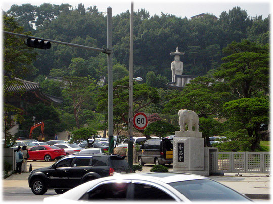 Photo of a buddhistic statue of Buddha in a park in the Seoul city center, surrounded by cars, buildings and offices. Foto von einer buddhistischen Statue mitten in der Stadt in Seoul.