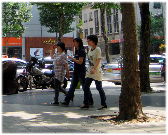 This photo shows city people walking in the shadow and hiding their face from the sun. Bild von jungen Koreanerinnen die sich vor der Sonne schützen
