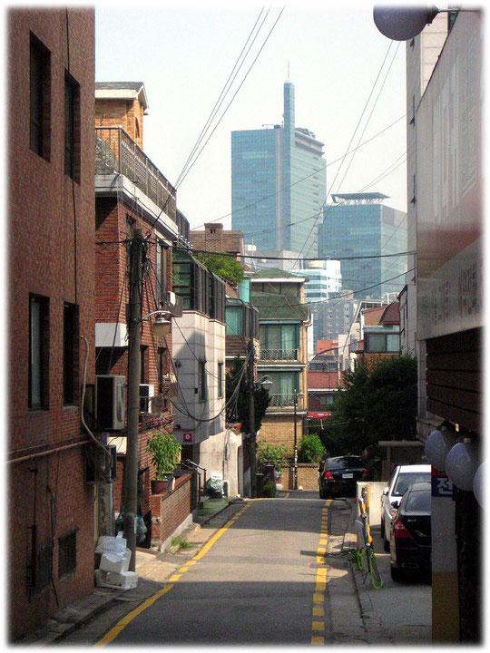 Photo of a narrow street surounded by high office buildings. Bild von einer sehr engen Straße und hohen Bürohäusern und Wolkenkratzern in der Umgebung
