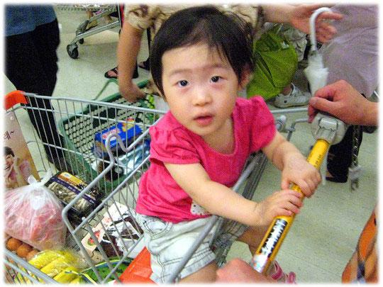 Photo of a small Korean boy sitting in the shopping cart at a South Korean shopping market. Foto eines koreanischen Kindes in einem Supermarkt Einkaufswagen.