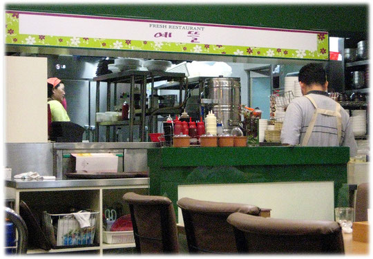 At this photo you see the kitchen of a restaurant with a big wide open window. Every guest can watch the cook cooking the food! Bilder vom asiatischen koreanischen Kochen in einer Küche