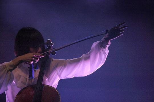 霧とリボン製ブルータッセルの指輪《ミドルフォンガー・ブローチ》が弓を持つ手に揺れています/Photo: Kiyo Murakami