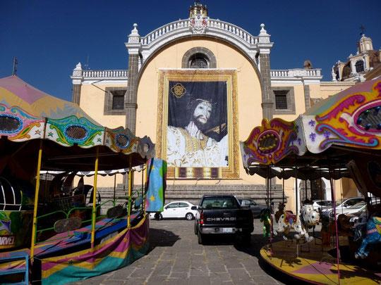 Effigie géante du Christ devant les manèges d'enfants, Puebla