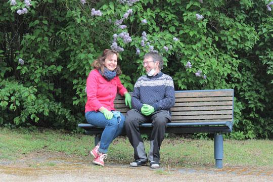 Pfarrerehepaar sitzt lächelnd auf einer Bank. Beide tragen grüne Einmalhandschuhe.  Hintergrund: Violett bühender Fliederbusch.