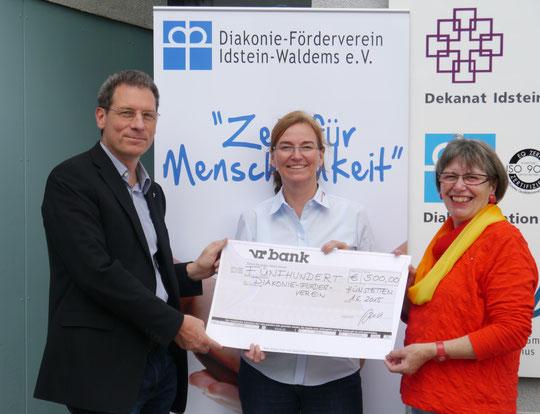 Bettina Meyer-Ried (2.v.l.) überreicht den symbolischen Scheck an Pfarrer Markus Eisele und Brigitte Krekel (Diakonie-Förderverein)