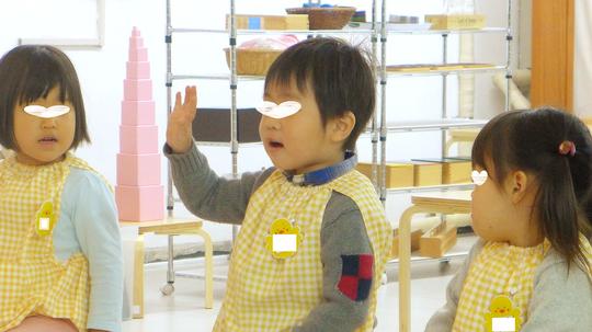 フィオーレコース(2歳児)のお友だちがリトミックで、自分で手をあげてしっかり返事をしています。