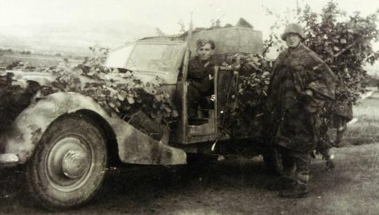 Lieutenant Lacoste debout près du véhicule dans le Cantal été 1944.
