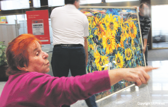 Bettina Heinen-Ayech setting up the exhibition in the foyer of the Stadtsparkasse Solingen