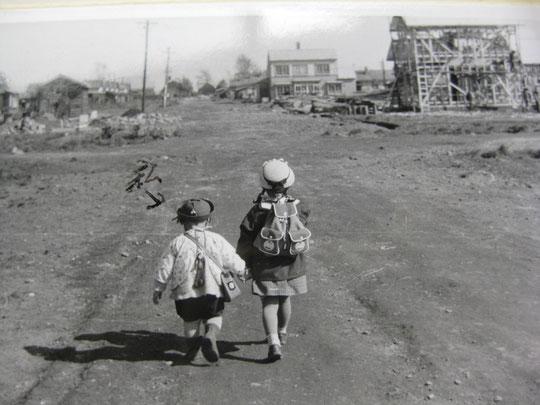 父が写した写真。姉の幼稚園の遠足についていくといってきかない典子。「私」の文字は父。