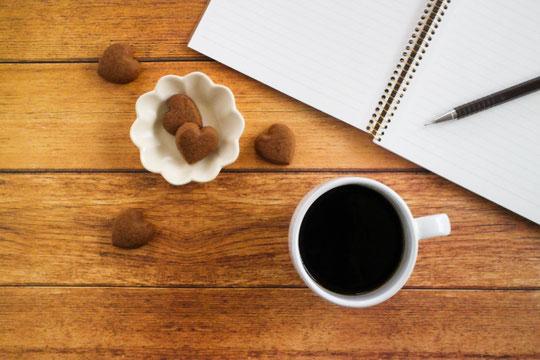 木目調のデスクに広げれらたノートとシャープペンシル。小皿に盛られたハート形のクッキーとコーヒーの入ったマグカップ。