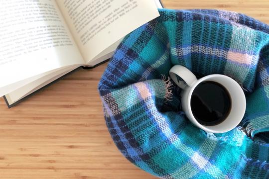 パソコンのキーボードの上に無造作に置かれたピンクのバラ。ゼムクリップが入った小さな缶。コーヒーの入ったマグカップ。