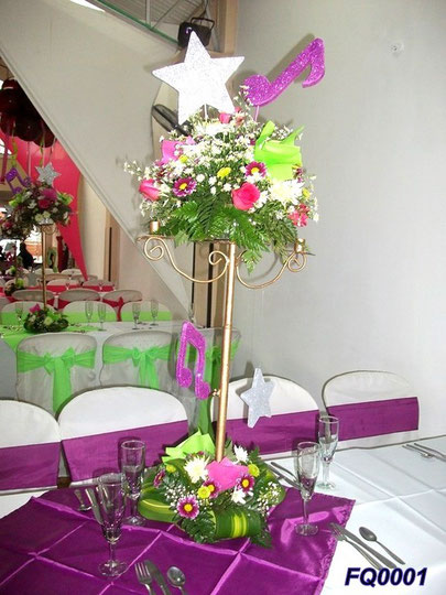 Centro de mesa con flores artificiales y decorado con cintas en variedad de colores, Todo  basado en piezas metalica y juegos de mesa.