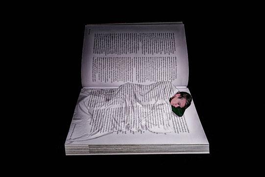 Une femme dort dans un lit aux draps imprimés comme s'il s'agissait d'un livre